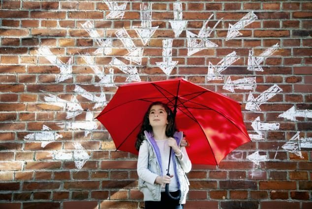 Young girl with red umbrella in front of brick wall surrounded by arrows