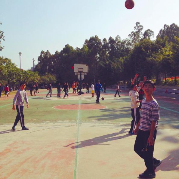 Китайские дети радуются появлению иностранца на спортивной площадке.