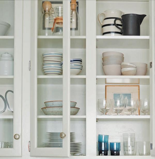 Тарелки и миски нейтральных цветов делают шкаф со стеклянными дверцами аккуратным.