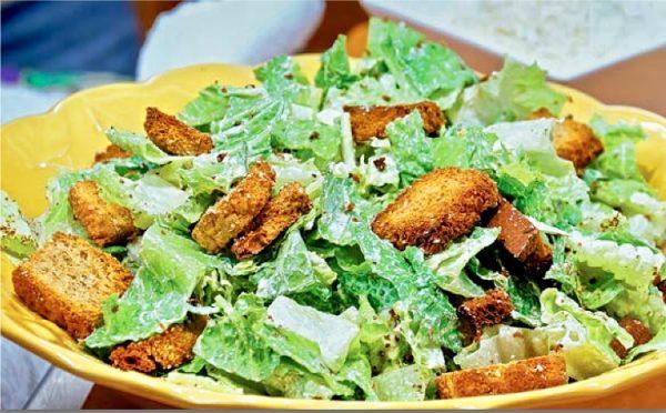 Хлеб порезать на небольшие кубики, смешать с приправами и выпекать в духовке при 200С до золотистого цвета. Дать остыть и смешать с листьями и соусом.