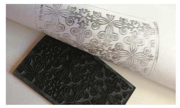 Натрите резиновый штамп пастелью и прикладывайте к бумаге, отпечатывая слова или орнаменты.