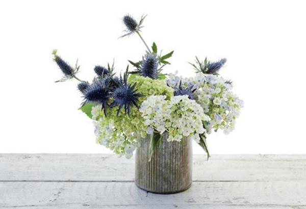 Освежите срезы у чертополоха и распределите цветы между гортензиями. Синие головки чертополоха должны возвышаться над базовыми цветами. (На одном стебле чертополоха растет несколько цветков, поэтому одни головки будут выше других.)
