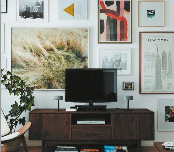 Окружите его полками. Повесьте телевизор на стену или поставьте на комод. Затем, разместив полки по обеим его сторонам, создайте фокусную стену. Оформите полки разными предметами и произведениями искусства, и телевизору будет сложно протиснуться в центр внимания.